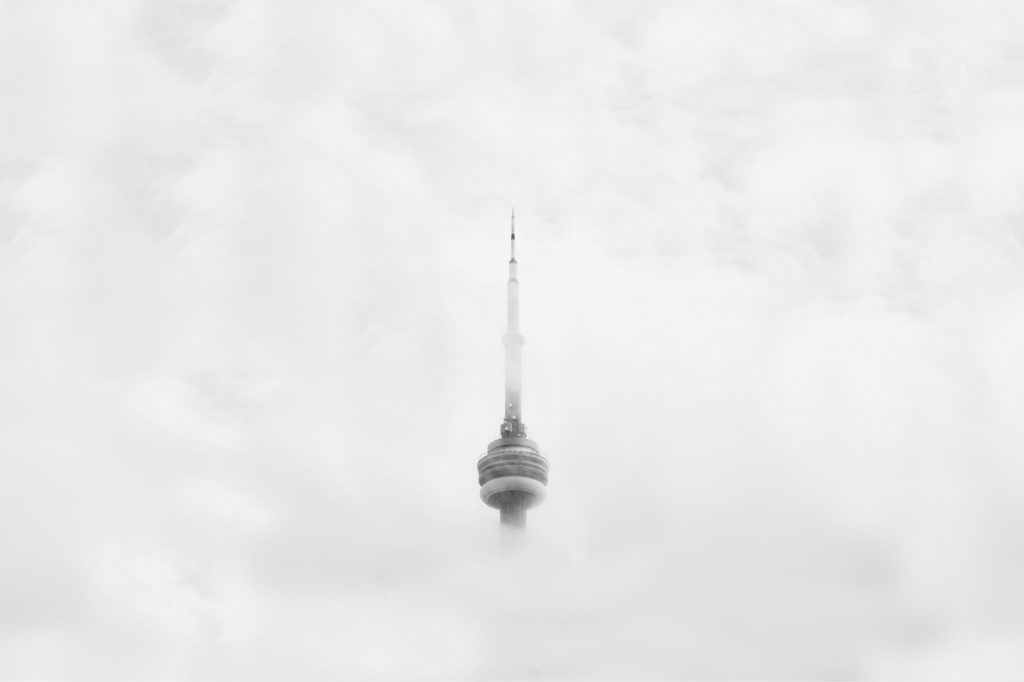 The C.N. Tower through grey clouds